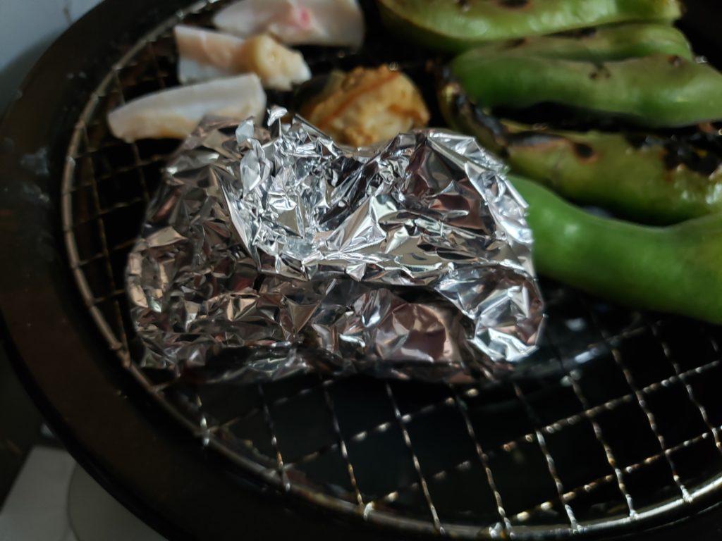 イカワタと足をホイルに包んだものを網焼きで焼く